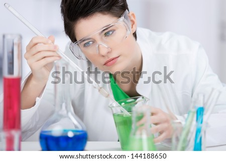 Attractive young female laboratory technician daring chemical tests leaning forwards to look at a solution in a large pipette