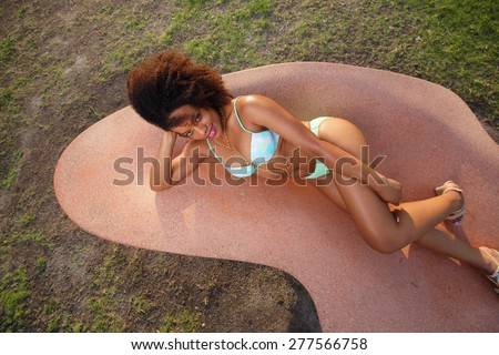 Attractive young female laying on a abstract park bench in her bikini - stock photo
