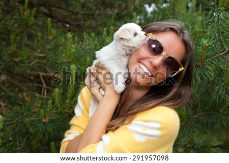 Attractive young female outside with her puppy. Cute puppy licking its attractive young female owner's face. - stock photo