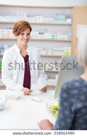 Attractive young female pharmacist standing holding a prescription smiling at the elderly patient, view over the shoulder of the patient - stock photo