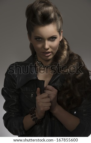 attractive young female posing with fashion dark look, black leather jacket and rock accessories with aggressive expression    - stock photo