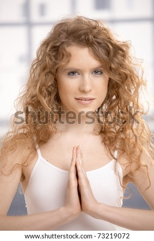 Attractive young female practicing yoga, meditating in prayer pose, eyes open, sitting on floor.? - stock photo