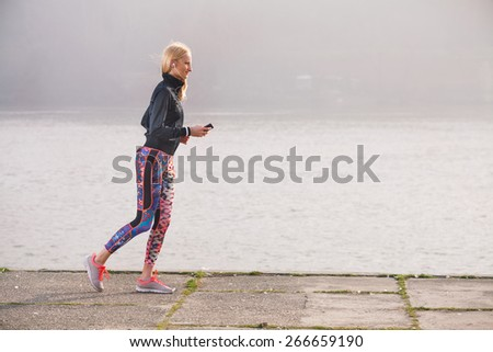 Attractive young female runner jogging  by the river and listening to music - stock photo