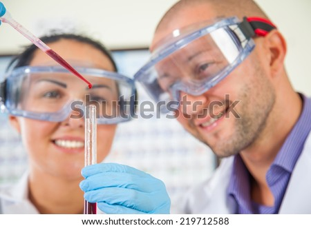 Attractive young female scientist and her male supervisor pipetting and microscoping in the life science research laboratory (biochemistry, genetics, forensics, microbiology..) - stock photo
