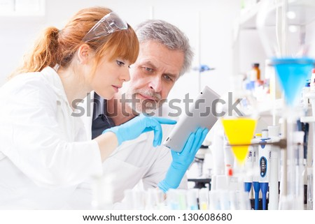 Attractive young female scientist and her senior male supervisor checking experiment protocol at tablet laptop computer in the life science research laboratory ( genetics, forensics, microbiology..) - stock photo