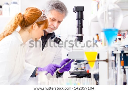 Attractive young female scientist and her senior male supervisor checking experiment protocol at tablet laptop computer in the life science research laboratory (bichemistry, genetics, forensics,..) - stock photo