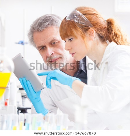 Attractive young female scientist and her senior male supervisor checking experiment protocol at tablet laptop computer in the life science research laboratory - stock photo