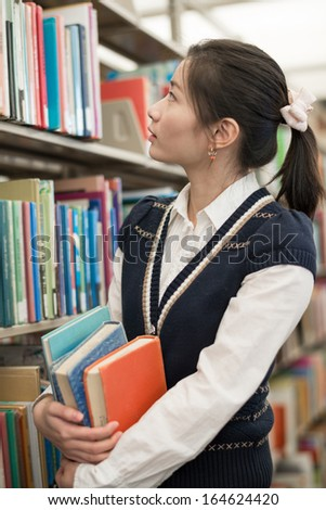 Attractive young female student holding a stack of books next to a bookshelf searching for books