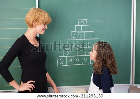 Attractive young female teacher and a cute young girl on maths class standing in front of the blackboard discussing a handwritten equation - stock photo