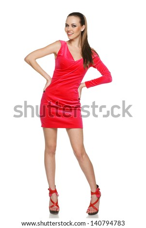 Attractive young female wearing pink cocktail dress posing on white background