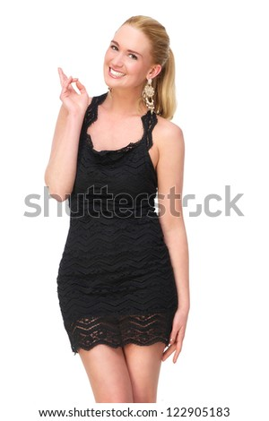 Attractive young female with a smile on her friendly face. She is pointing up with her fingers. Possible copy space. Isolated on white background