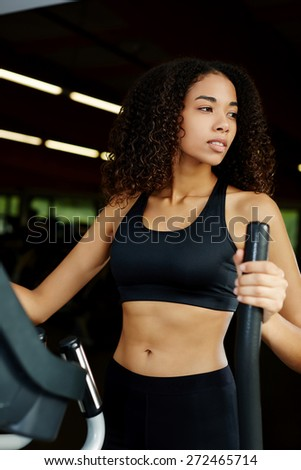 Attractive young fitness model exercising on machine in fitness center - stock photo