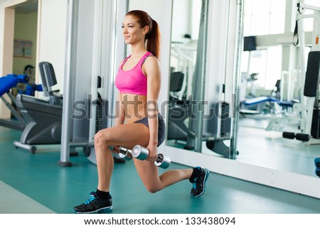 Attractive young fitness model works out with dumbbells in fitness center - stock photo