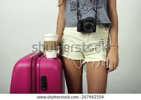 Attractive young girl going on vacation with suitcase and camera. - stock photo