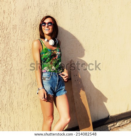 Attractive young girl hipster posing by the wall in summer hot weather with travel bag and longboard . Listening music having fun and laughing   - stock photo