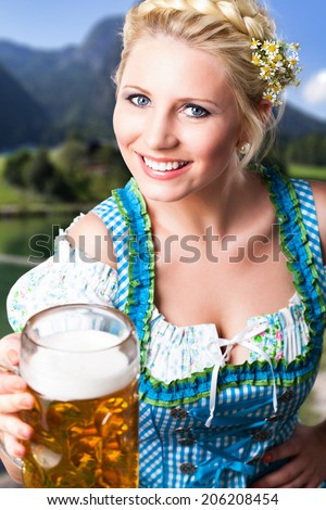 attractive young girl in a dirndl with a beer - stock photo