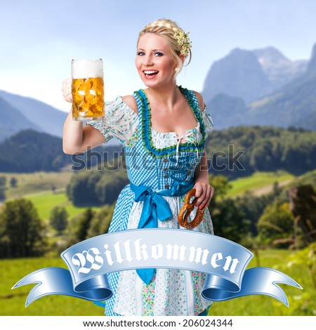 attractive young girl in a dirndl with a beer and a badge stating welcome in German - stock photo