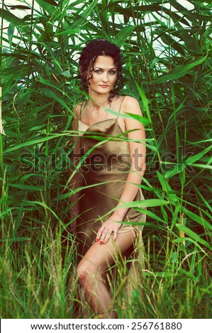 Attractive young girl in an olive dress posing over green plants. Fashion portrait. Outdoor shot