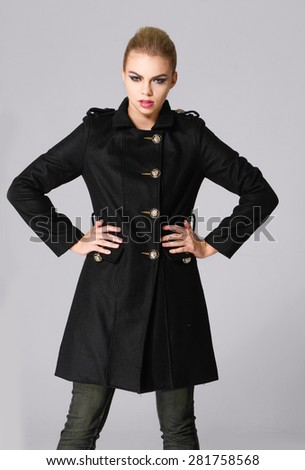 attractive young girl in black coat posing-gray background - stock photo