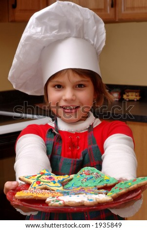 Attractive young girl in chef's hat offering viewer a plateful of cookies she'd decorated herself. - stock photo