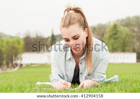 Attractive young girl lying on grass and writing in notebook outside in a spring day - stock photo