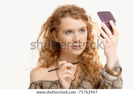 Attractive young girl making up her face, looking herself in mirror. - stock photo