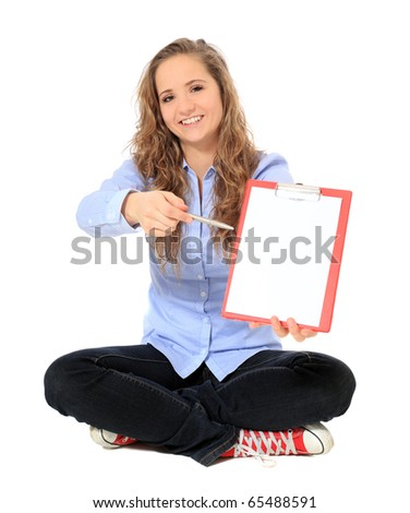 Attractive young girl pointing with pen on clipboard. All on white background. - stock photo