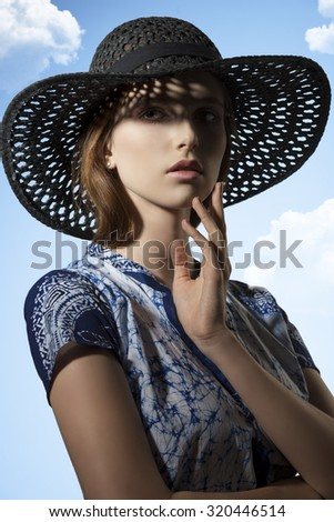 attractive young girl posing in fashion shoot with trendy shirt and elegant hat, looking in camera.   - stock photo