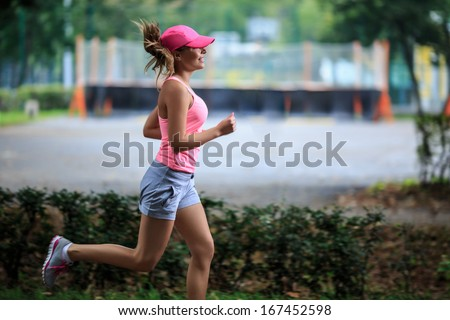 Attractive young girl running in park - stock photo