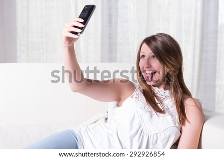 attractive young girl shooting selfie with tongue out - stock photo
