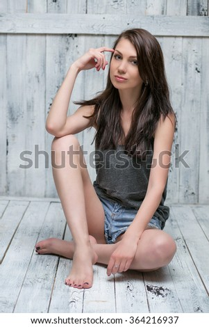 Attractive young girl sitting in the studio on a wooden floor