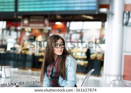 Attractive young girl sitting on the transparent chair, looking away. High-tech cafe design in the background.
