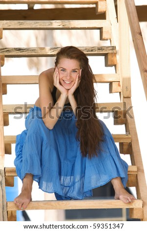 attractive young girl sitting on wooden stairs - stock photo