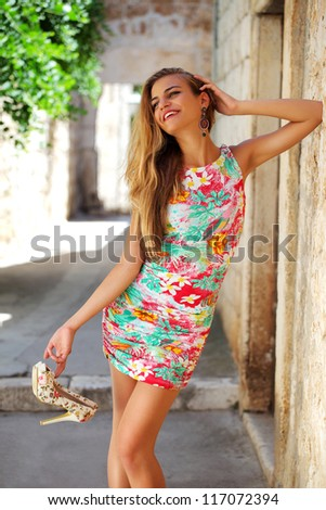 Attractive young girl standing by the stone wall in old mediterranean town - stock photo