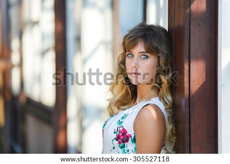 Attractive young girl standing near an abandoned house - stock photo