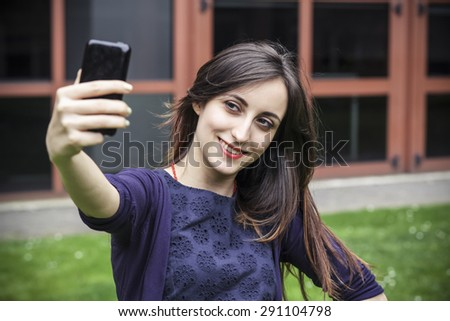 Attractive young girl takes a selfie with a smart phone - stock photo