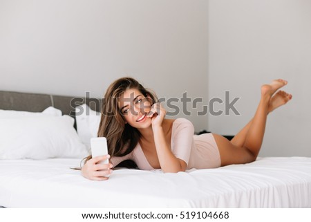 Attractive young girl taking selfie on phone on bed in apartment in the morning