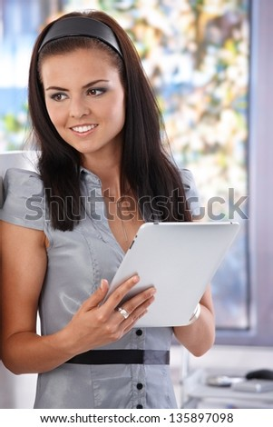 Attractive young girl using tablet computer, smiling, looking away.