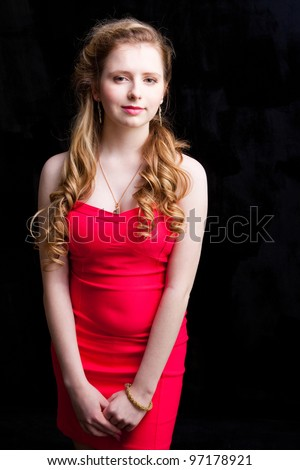 attractive young girl with long blonde hair wearing short red dress on black background