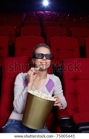 Attractive young girl with popcorn watching a movie at the cinema - stock photo