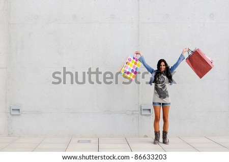 Attractive young girl with shopping bags in the street - stock photo