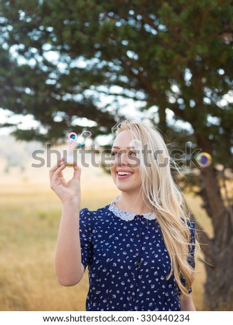 attractive young girl with soap-bubbles in nature - stock photo