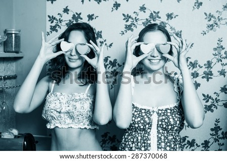Attractive young girls holding pink hearts over eyes in the kitchen - stock photo
