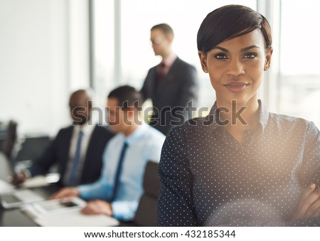 Attractive young grinning business owner in office with polka dot blouse, folded arms and confident expression in front of group of employees at conference table - stock photo