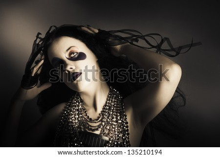 Attractive young grunge fashion girl in bright cosmetics with curly black hairstyle and expensive silver jewelry chain - stock photo
