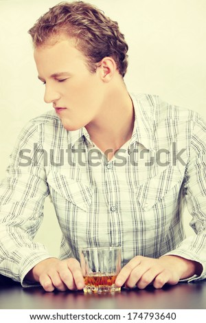 Attractive young guy drinking whiskey - depressed  - stock photo