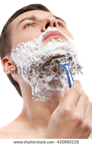 Attractive young guy is shaving in morning - stock photo
