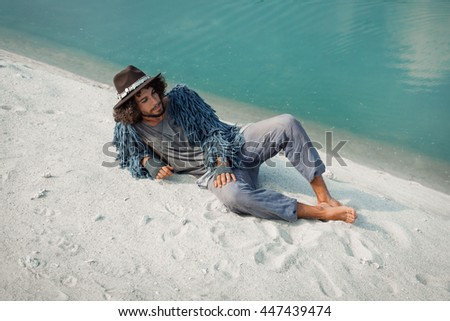 Attractive young gypsy man lying on sand at lake shore