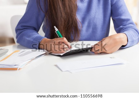 Attractive young Hispanic woman sitting at table paying bills and doing banking wearing blue sweater.