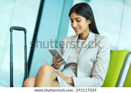 attractive young indian businesswoman using smart phone at airport - stock photo